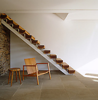 A Charlotte Perriand stool and Knoll chair sit beneath a staircase made from slabs of unfinished walnut resting on a metal frame