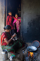 Pinki Khristi, 28, cooks a meal for her family while her daughter (left) plays with a neighbour at their farm house in Anand, Gujarat, India on 9th December 2012. Pinki's sister-in-law had convinced her to become a surrogate together with her in 2008 and Pinki has since done 2 surrogacies. While Pinki and her husband Dhiraj used to make 2000-5000 rupees per month from farming and as labourers, she had made over 850,000 from both her surrogacies and had bought land, buffaloes and saved 320,000 rupees in a fixed deposit. Photo by Suzanne Lee / Marie-Claire France
