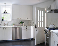 In the contemporary kitchen stainless-steel appliances are paired with white cabinets and a marble worktop