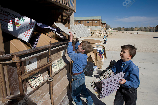 """Fundamentalist Mormon group F.L.D.S.,  boys load cardboard into the recycler at the Storehouse on the """"Yearning for Zion"""" compound in Eldorado, Texas, USA, February 12, 2009"""