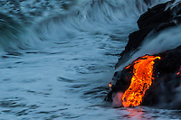 Between sunset and dusk, glowing lava flows into the Pacific Ocean from the Big Island of Hawai'i.