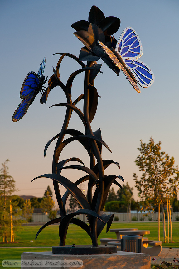 The butterfly statue at Stanton Central Park, seen at sunset with some park tables, trees, and a grassy lawn in the background in front of a clear blue sky.  The statue is made of blue glass, stainless steel, and black iron.