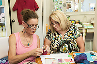 STAFF PHOTO ANTHONY REYES &bull; @NWATONYR<br /> Loralee Canfield, left, owner of the Mockingbird Moon, helps Carol Vick, of Rogers, with a knitting project Thursday, Sept. 18, 2014 during a crocheting and knitting class at Mockingbird Moon in Rogers.