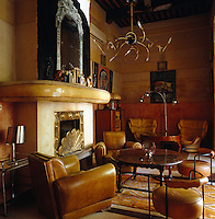 "1920s leather chairs and Joe Colombo ""Elba"" chairs fill this sitting area which features a brass-detailed fireplace"