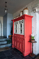 An Irish vernacular cabinet in the family entrance hall has been painted a scarlet red