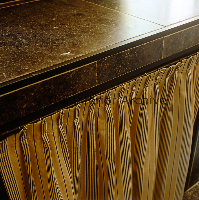 Granite work tops in the kitchen are softened with a curtain of striped fabric which conceals the open shelving