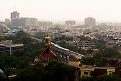 Metro trains criss cross against the foreground of the statue of Hindu God, Hanuman in New Delhi, India.
