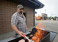 NWA Democrat-Gazette/BEN GOFF @NWABENGOFF<br /> Shawn Gaines volunteers on the grill for the concessions stand Monday, April 17, 2017, before the Bentonville High vs Rogers High baseball game at the Tiger Athletic Complex in Bentonville.