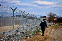 Greek policeman checks the fence between Greece and the Republic of Macedonia in Idomeni, 8 Febraury 2016.<br /> Hundreds of refugees arrive at Idomeni and cross the border between Greece and Macedonian on their journey to North Europe.