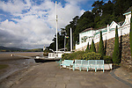 "Portmeirion, in North Wales, is a resort, where no one has ever lived. A self-taught Welsh architect named Sir Clough Williams-Ellis built it out of architectural salvage between the 1920s and 1970s, loosely based on his memories of trips to Portofino. Including a pagoda-shaped Chinoiserie gazebo, some Gothic obelisks, eucalyptus groves, a crenellated castle, a Mediterranean bell tower, a Jacobean town hall, and an Art Deco cylindrical watchtower. He kept improving Portmeirion until his death in 1978, age 94. It faces an estuary where at low tide one can walk across the sands and look out to sea. At high tide, the sea is lapping onto the shores. Every building in the village is either a shop, restaurant, hotel or self-catering accomodation. The village is booked out at high season, with numerous wedding receptions at the weekends. Very popular amongst the English and Welsh holidaymakers. Many who return to the same abode season after season. Hundreds of tourists visit every day, walking around the ornamental gardens, cobblestone paths, and shopping, eating ice-creams, or walking along the woodland and coastal paths, amongst a colourful assortment of hydrangea, rhododendrons, tree ferns and redwoods. The resort boasts two high class hotels, a la carte menus, a swimming pool, a lifesize concrete boat, topiary, pools and wishing wells. The creator describes the resort as ""a home for fallen buildings,"" and its ragged skyline and playful narrow passageways which were meant to provide ""more fun for more people."" It does just that.///'Amis Reunis' Stone boat construction on the quayside to the estuary below the Portmeirion Hotel"