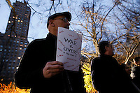 A Fan holds a poster next to a memorial set up for John Lennon around the 'Strawberry Fields' in Central Park during the 35-year anniversary of his death in New York December 8, 2015. The death of John Lennon still reverberates as a defining moment for a generation and for the music world. Police said the shooting occurred outside the Dakota, the century-old luxury apartment house where Lennon and his wife, Yoko Ono, lived. It is across the street from Central Park. Kena Betancur/VIEWpress.