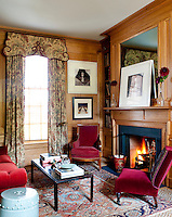 In the reading room the wood panelled walls are paired with red velvet upholstered chairs