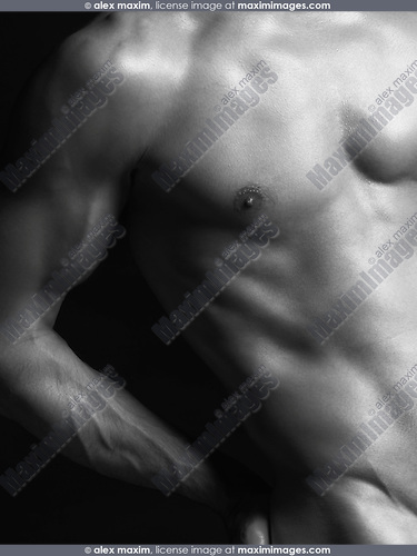 Closeup of young nude man fit naked body on black background artistic black and white photo