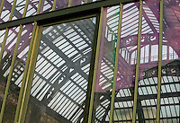 New Caledonia Glasshouse (formerly The Mexican Hothouse), 1834-36, Rohault de Fleury, Jardin des Plantes, Museum National d'Histoire Naturelle, Paris, France. Low angle view, through a door, to the roof of the glass and metal structure lit by the afternoon light in winter.