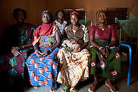 "9 December 2009, Banikoara, Benin. Community Health Clinic ""Comparou Maternité."" The clinic delivers a wide variety of services including delivering of babies and ante-natal checkups. The mothers-to-be are given an ante-natal package of folic acid, mosquito nets and malaria prophylactics. If there is an emergency, an ambulance can take them to the main hospital.19 year-old Estelle Agbla gave birth to her firstborn the previous evening and proud family members gather to celebrate the arrival."
