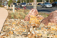 A view of the gorgeous rocks that make up a dominant element of the landscaping of the Harbor Boulevard Cornerstone Bike Trail in Costa Mesa, California under a clear blue sky.  The landscaping rocks play the primary visual role in this image, but many cars driving along the street are visible subtly blurred in the background.  The path is minimized in this view.  The landscape architecture work on the project was done by David Volz Design.