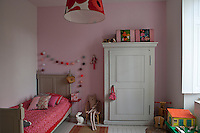 A French bed complemented by a grey-painted antique armoire and pink accessories furnishes this child's bedroom