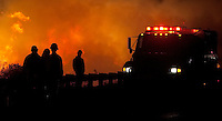 A group of firefighters watch flames that flared up along Highway 8 in the eastern part of San Diego County, California on October 28, 2003. The fires in San Diego have burned more than 300,000 acres and destroyed hundreds of homes.