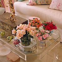 Small vases of roses and carnations decorate the Perspex coffee table