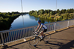 A cyclist crosses a bridge over the American River while riding the American River Bike Trail in Sacramento, California.