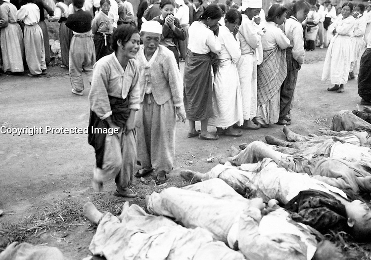 Koreans from Hamhung identify the bodies of some 300 political prisoners who were killed by the North Korean Army by being forced into caves which were subsequently sealed off so that they died of suffocation.  October 19, 1950.  Lt. Winslow. (Army)<br /> NARA FILE #:  111-SC-351359<br /> WAR &amp; CONFLICT BOOK #:  1508