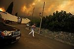 SPAIN, Mombeltran : A woman runs in a street to escape from a wildfire in Mombeltran near Avila, on July 28, 2009. (C) Pedro ARMESTRE