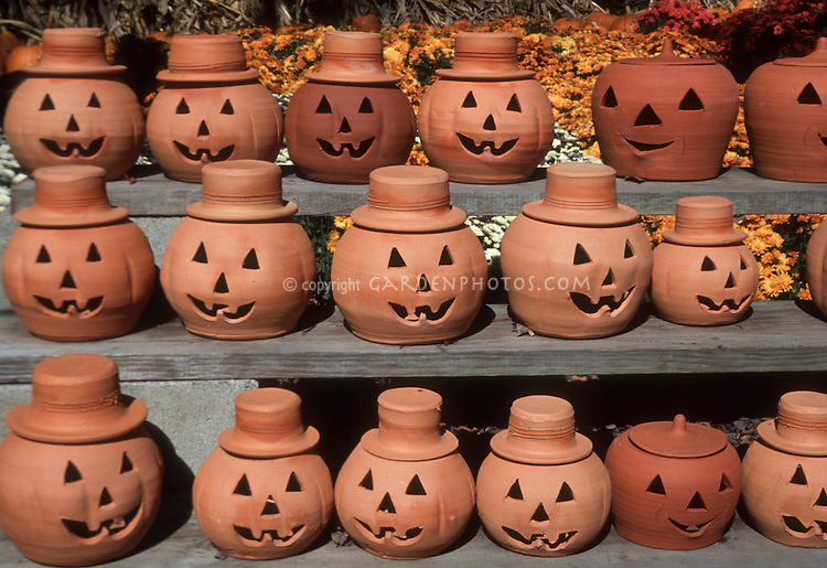 Pumpkins made of terracotta on benches in autumn for Halloween decorations