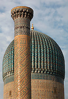 Detail of dome and minaret, Gur-Emir Mausoleum, 1404, Samarkand, Uzbekistan, pictured on July 15, 2010, at dawn. Gur-Emir Mausoleum, or Tomb of the Ruler, was built by Timur in 1404 for his favourite grandson, Mohammed Sultan, and became the mausoleum for the Timurid dynasty. The simply formed building is an octagonal drum beneath an azure fluted dome (diameter: 15m, height: 12.5m). Its walls are tiled in blue and white geometric and epigraphic patterns including the words 'God is Immortal' in 3m. high white Kufic script around the top of the drum. Samarkand, a city on the Silk Road, founded as Afrosiab in the 7th century BC, is a meeting point for the world's cultures. Its most important development was in the Timurid period, 14th to 15th centuries. Picture by Manuel Cohen.
