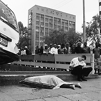 A crowd of people watch as a policeman writes a report about a road traffic accident at the junction of Rissik and Wolmarans Streets. The accident involved a taxi and there is a fatality lying on the pavement covered by a plastic sheet.