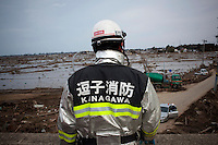A member of a rescue team looks over the debris as other members clear roads and search for bodies. On 11 March 2011 a magnitude 9 earthquake struck 130 km off the coast of Northern Japan causing a massive Tsunami that swept across the coast of Northern Honshu. The earthquake and tsunami caused extensive damage and loss of life.
