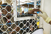 Somaliland. Waqohi Galbed province. Hargeisa. Tubeculosis (TB) hospital. A young black muslim man, suspected tuberculosis (TB) case, gives through a barred window sputum in a plastic sputum cup to a nurse, wearing plastic glove on her hand. The Global Fund through the ngo ( non-governmental organization ) World Vision supports the programm with a Tuberculosis grant (financial aid). Somaliland is an unrecognized de facto sovereign state located in the Horn of Africa. Hargeisa is the capital of Somaliland. © 2006 Didier Ruef