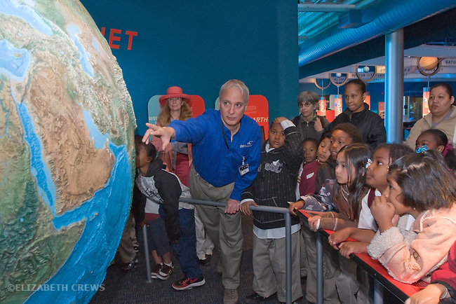 Oakland CA Docent illustrating concepts about solar system and earth's place in it to group of second grade students on field trip to the Chabot Space and Science Center