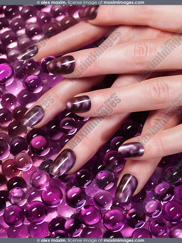 Closeup of woman hand with custom design purple nail polish on abstract purple background