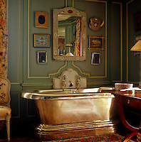 An ornate mirror from Agra hangs above the stunning silver-plated copper bath in the master bathroom
