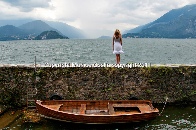 A girl stands on a stone wall by the water and sees a storm coming; Varenna on Lake Como, Italy