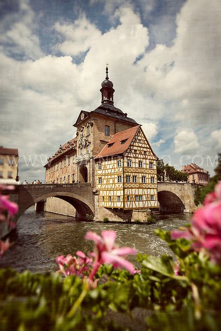 Scenic view of the Old City Hall in Bamberg, Germany, sitting on the Regnitz River with pink flowers in the foreground.