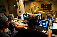 San Francisco, California, January 6, 2011 - University of California San Francisco Medical Center staff (from left), chief resident Mark Richardson, Alastair Martin PhD in the Department of Radiology and neurologist Paul Larson MD monitor the iMRI procedure of patient Linda Sharpe during an iMRI surgery at University of California San Francisco Medical Center. The MRI machine photographs the patient during the surgery allowing the doctors operating to view the procedure as well as support doctors and technicians to monitor from an outside room.  The iMRI procedure uses Deep brain stimulation (DBS), which has been used for over a decade to treat movement disorders such as Parkinson's disease, essential tremor, and dystonia. DBS uses a pulse generator implanted in the chest, similar to a pacemaker, to deliver pulses to specific regions of the brain via a permanently implanted electrode. In the U.S., DBS is normally done while the patient is awake, because the surgeon needs to induce the symptoms (like the involuntary movements of Parkinson's) to know if he's in the right place, and if the patient is unconscious, the symptoms can't be induced. Many patients find it hard to tolerate. Their head is clamped in a frame, they're aware of their surroundings, and the surgeon is deliberately producing tremors and twitches while they lie there...Interventional MRI (or iMRI) allows surgeons to implant these electrodes while the patient is unconscious taking advantage of MR imaging in real time by performing procedures inside the scanner itself. Doctors Paul Larson MD, and Philip Starr MD, PhD were both involved with this technology during its development in the 1990s. In 2002 they began to think about how to perform DBS using this technique at UCSF. Working with Alastair Martin PhD in the Department of Radiology, Jill Ostrem MD in the Department of Neurology, and others, they developed a technique of implantation using a modified but commercially available skull-mounted aiming