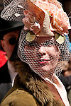 A woman in the Easter Parade in New York City wearing a straw hat with large pink roses on it and a delicate beige net over her face