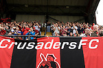 Crusaders supporters cheering their team on to the pitch at Seaview Park, Belfast before the Northern Irish club take on Fulham in a UEFA Europa League 2nd qualifying round, fist leg match. The visitors from England won by 3 goals to 1 before a crowd of 3011.