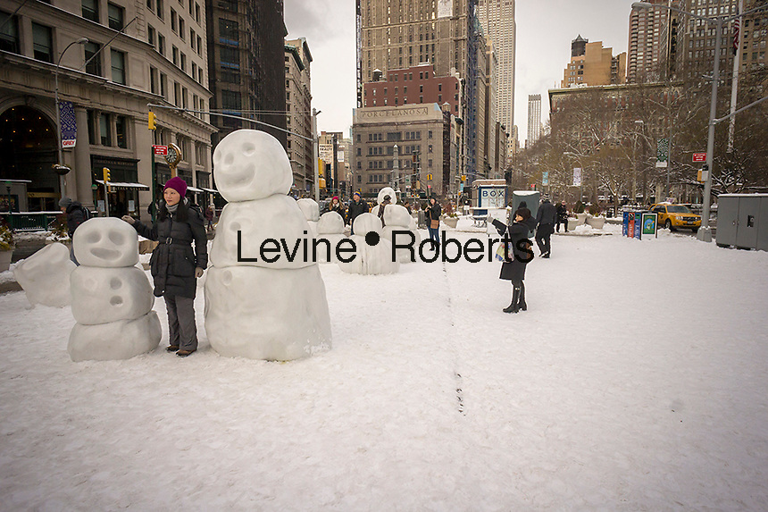 "Visitors to Flatiron Plaza in New York on Tuesday, January 27, 2015 make up for the lack of snow from winter storm Juno by interacting with ""Snow Monsters"" by the artist Peter Regli. The 12 marble snowmen are part of the artists ""Reality Hacking"" project and will be on view until March 13.(© Richard B. Levine)"