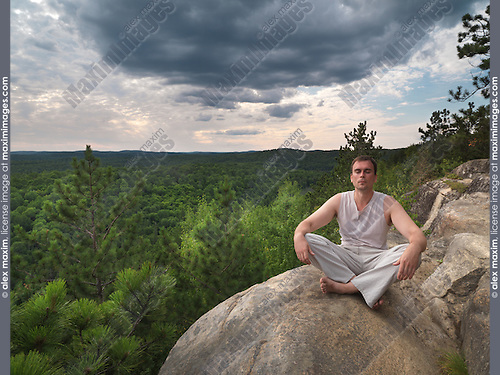 Young man meditating in the nature. Algonquin, Ontario, Canada.