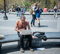 A topless visitor to Washington Square Park in New York City takes advantage of the free wifi on his MacBook and enjoys the spring weather on Thursday, May 1, 2014.  Temperatures are expected to rise into the 70's today after more than 24 hours of rain which dumped 4 inches in Central Park.  (© Richard B. Levine)