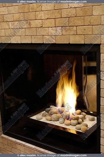 Contemporary natural gas fireplace with glass from both side of the wall