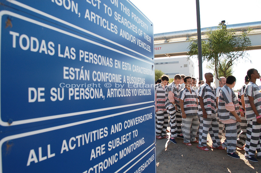 """Phoenix, Arizona. April 17, 2009 - Nine hundred Maricopa County Jail pre-sentenced male inmates were moved from one housing facility to another in the massive Maricopa County Jail Complex, located in southwest Phoenix . The 900 inmates walked in chains wearing their black and white striped jail uniforms from the Lower Buckeye Jail and the Towers facility. According to the Maricopa County Sheriff's Office (MCSO), moving these inmates opened up 200 more beds for medium and maximum security jail inmates. In a press release, Maricopa County Sheriff Joe Arpaio said: """"For 16 years, I've had a vacancy sign shining over Tent City to tell everybody we will always find a way to make room for more law breakers. Even in hard times like these, I'm not about to allow the early release of inmates because we run out of bed space for bad guys."""" The transfer of inmates was overseen by Sheriff Arpaio and secured by the Sheriff's SWAT and Special Response teams as well as deputies and armed posse. Just a few weeks before, Sheriff Arpaio was criticized for what was considered the parading another 220 jail inmates from one jail to the Tent City Jail. Photo by Eduardo Barraza © 2009"""