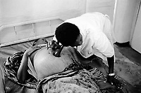 Burundi. Karuzi Province. Buhiga. Hospital. A nurse tries to hear the sounds of a baby's health whose mother is nine months pregnant. © 2000 Didier Ruef