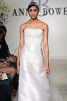 "Model walks runway in a Virtue Bridal dress - orchid white crystal beaded bodice, silk and wool strapless A-line gown with tulle train, and clear crstal belt, from the Anne Bowen Bridal Spring 2013 ""Coat of Arms"" collection fashion show, during Bridal Fashion Week New York April 2012."