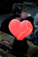 Heart shaped lamp. One of the world's largest convention of computer enthusiasts, simply called 'The Gathering'. Over five thousand young people come together each Easter, some travelling long distances, each carrying their own computer equipment to the massive Vikingship sports hall in the city of Hamar. The main activity is online gaming. Many hardly see daylight or taste fresh air for the entire five days as they compete with their fellow geeks for cash prizes and the honour of being the best.