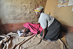 Home-based care worker Olipa Mkandawire (right), prays for a man living with AIDS in Matuli, Malawi. She represents the Livingstonia Synod AIDS Program of the Church of Central Africa Presbyterian.
