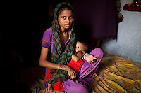 Sadma Khan, 19, breastfeeds her 18 month old child in her mother's one-room house she shares with the rest of her immediate family in a slum area of Tonk, Rajasthan, India, on 19th June 2012. She was married at 17 years old to Waseem Khan, also underaged at the time of their wedding. The couple have an 18 month old baby and Sadma is now 3 months pregnant with her 2nd child and plans to use contraceptives after this pregnancy. She lives with her mother since Waseem works in another district and she can't take care of her children on her own. Photo by Suzanne Lee for Save The Children UK