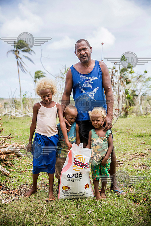 Jean Paul, 45, with his children (L-R) eight year old Belonet, four year old Alfred and two year old Janou. Their garden, where they grow food, was destroyed by Cyclone Pam on 13 March 2015. They came with their father to a local grocery shop on outskirts of Port Vila to receive bags of rice being distributed as aid.